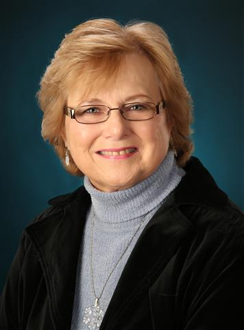 Older female with short blond hair and glasses