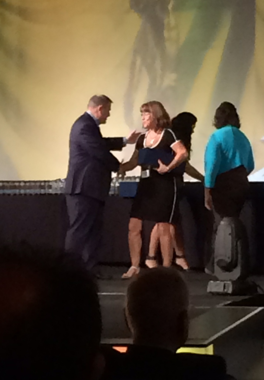 man handing an award to a woman in a black dress
