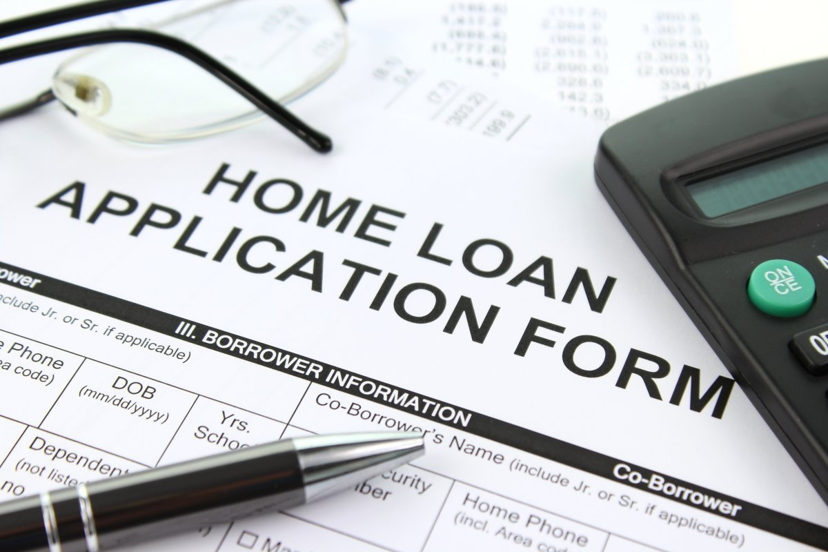 Home Mortgage Application form with pen and calculator.